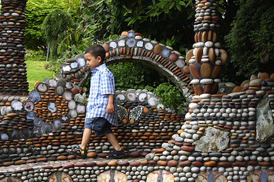 Boy walking through rock garden