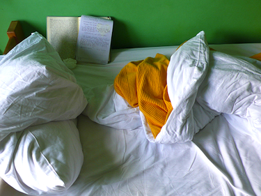 Sick bed, sheets, notebooks, tissues.