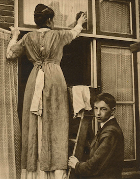 1914 photo of woman washing windows, boy helping